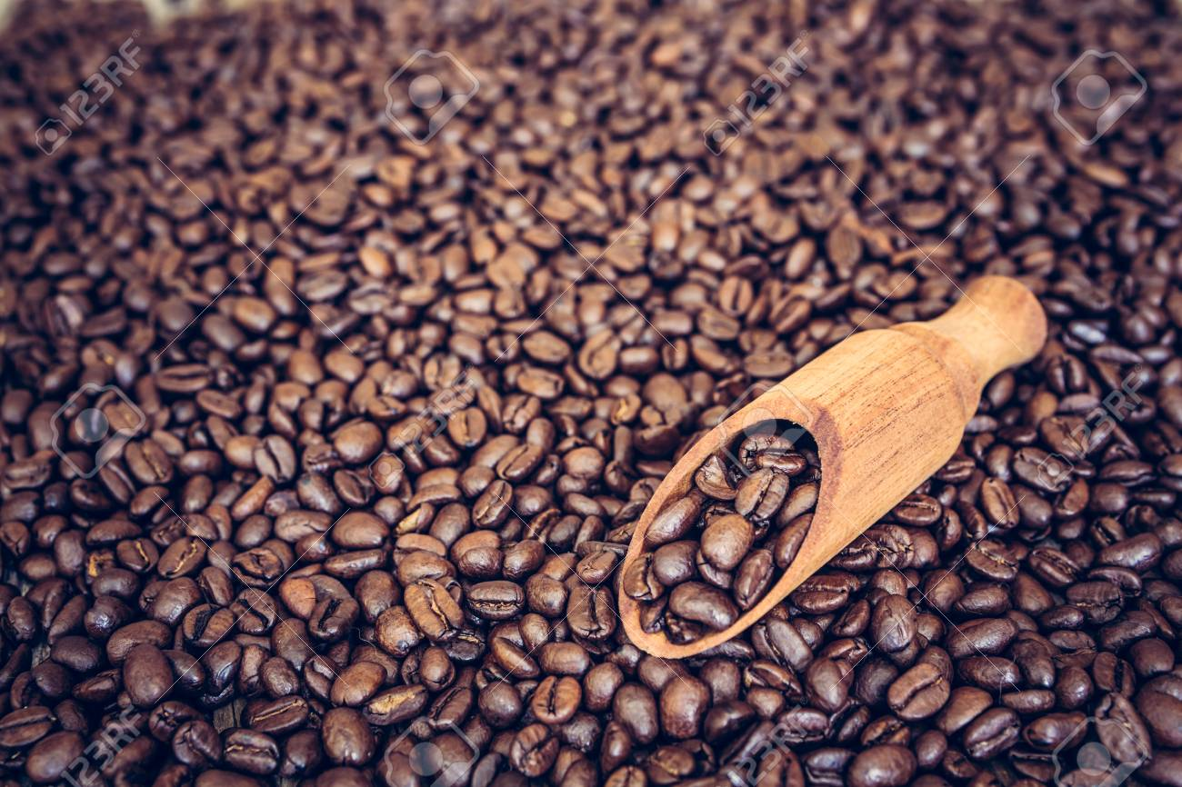 Wooden scoop full of coffee beans on roasted coffee beans background - 97426323