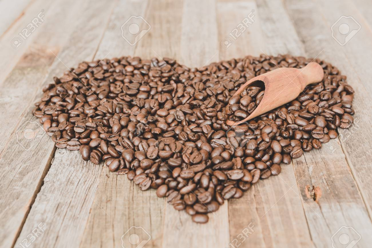 Roasted coffee beans in a shape of heart on wooden background - 97431643