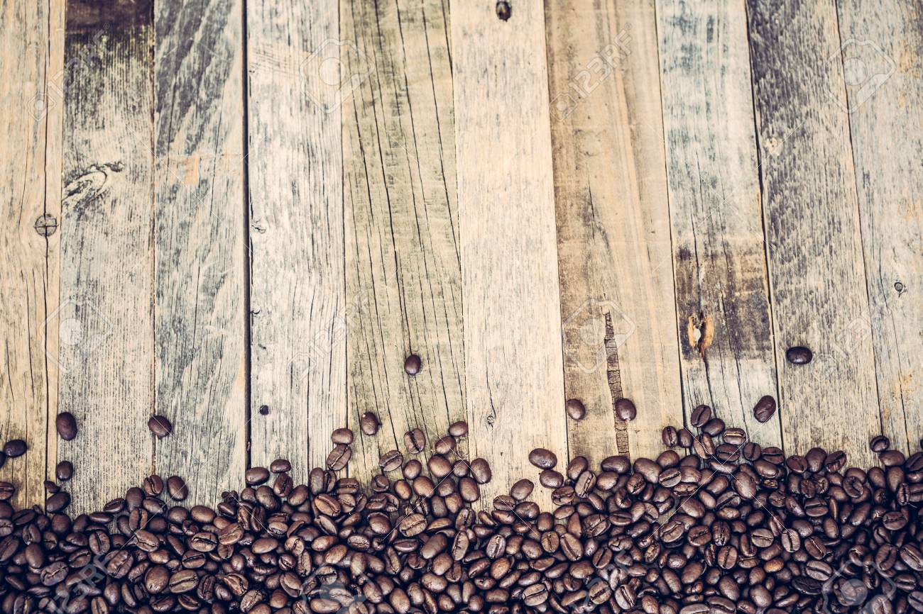 Roasted coffee beans spread on bottom part of wooden table background - 97431647