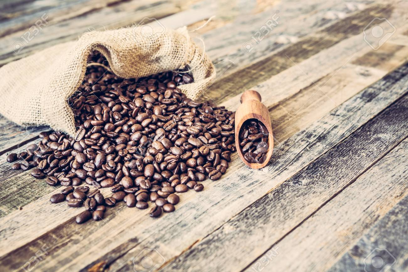 Roasted coffee beans in a burlap bag on wooden table background - 97426324