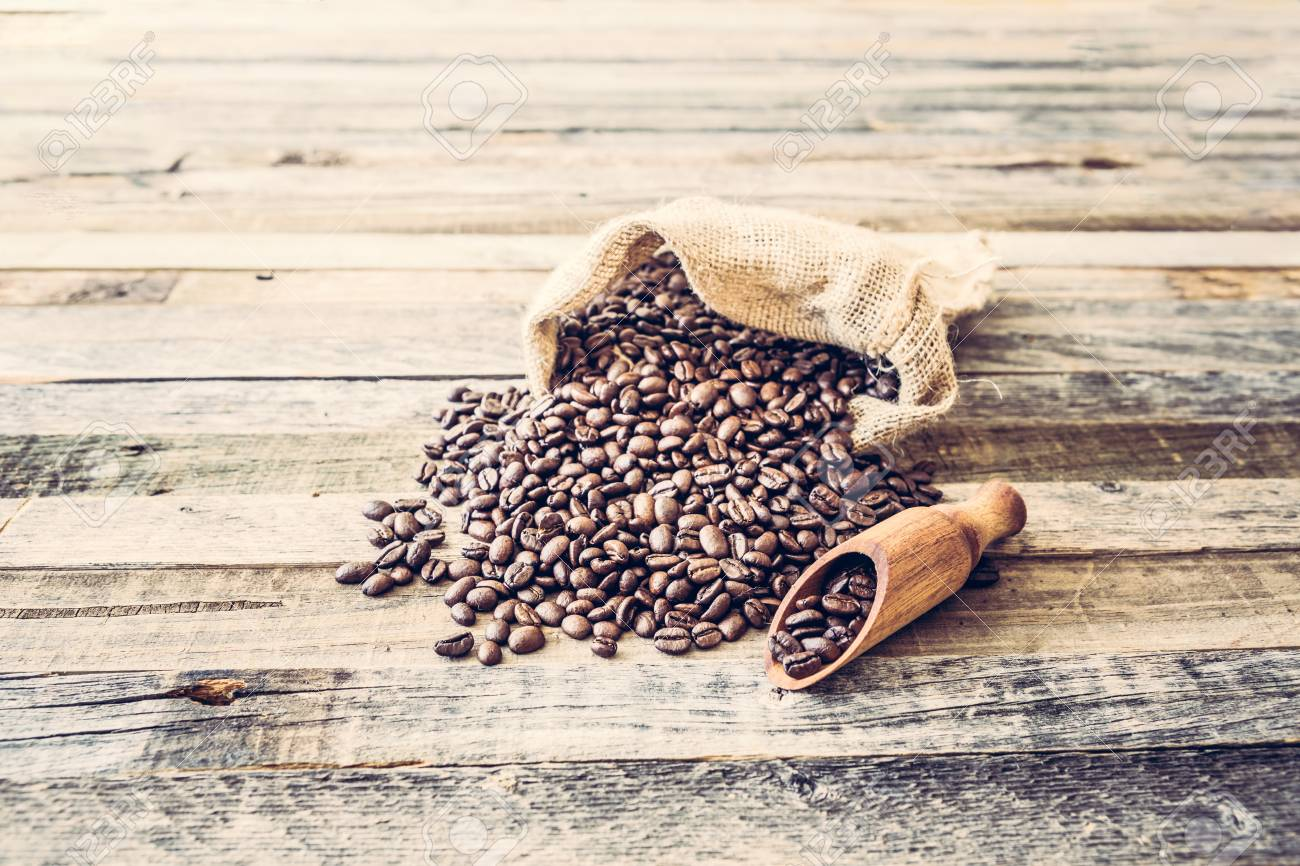 Roasted coffee beans in a burlap bag on wooden table background - 97431649