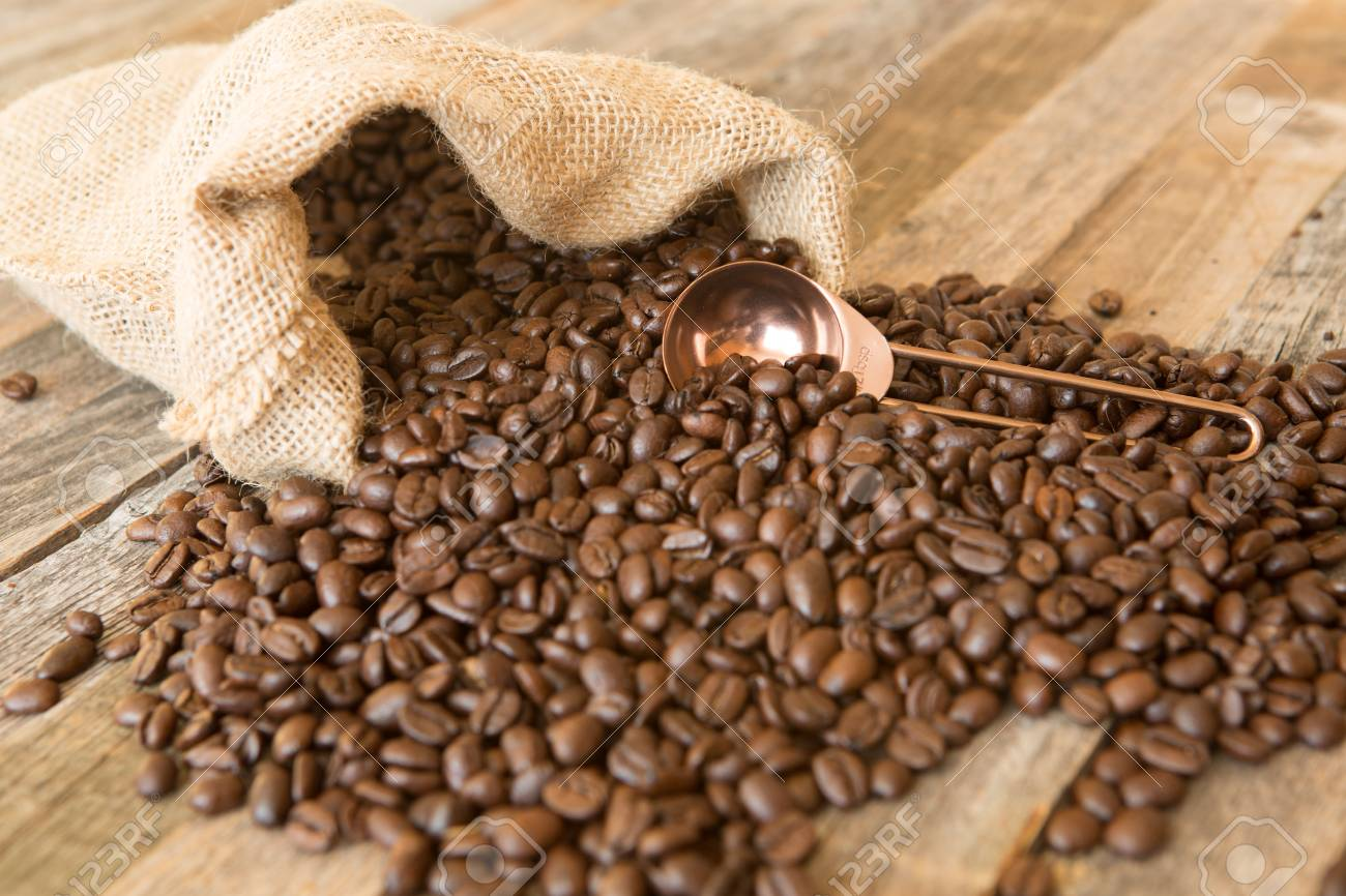 Roasted coffee beans in a burlap bag on wooden table background with copper scoop - 97426326