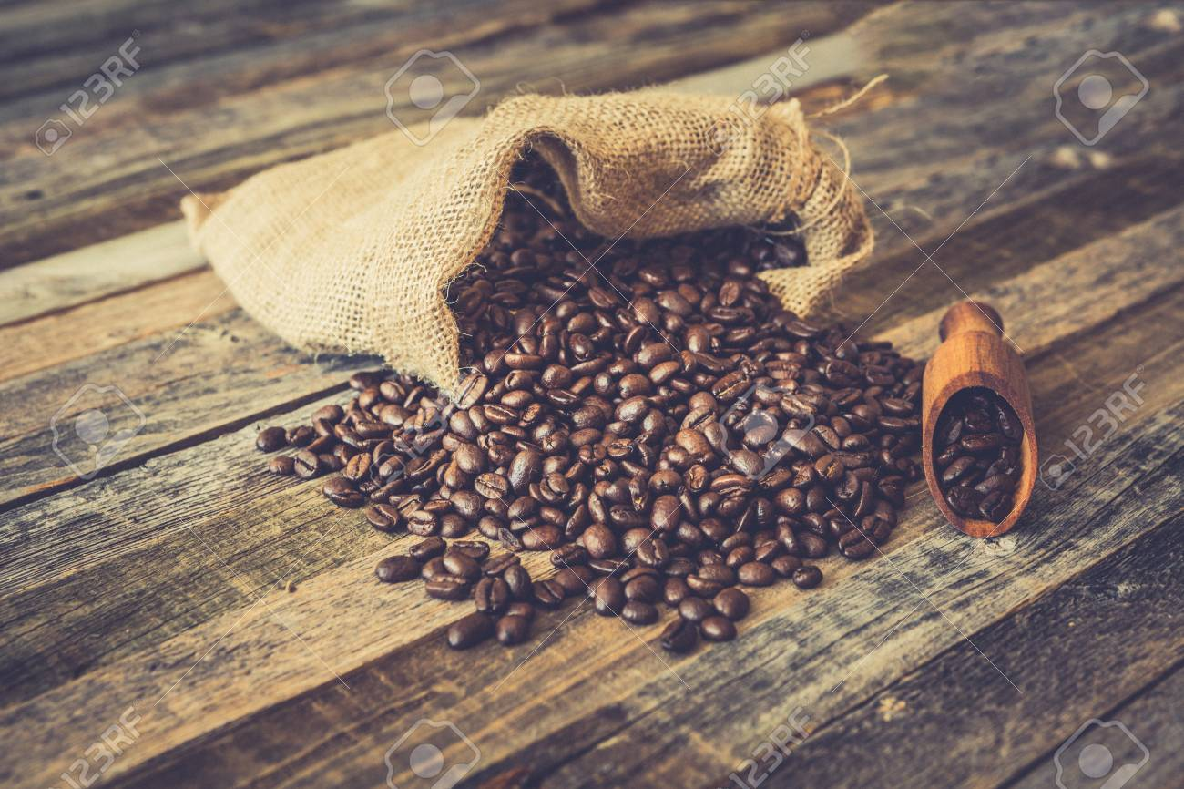 Roasted coffee beans in a burlap bag on wooden table background - 97431656