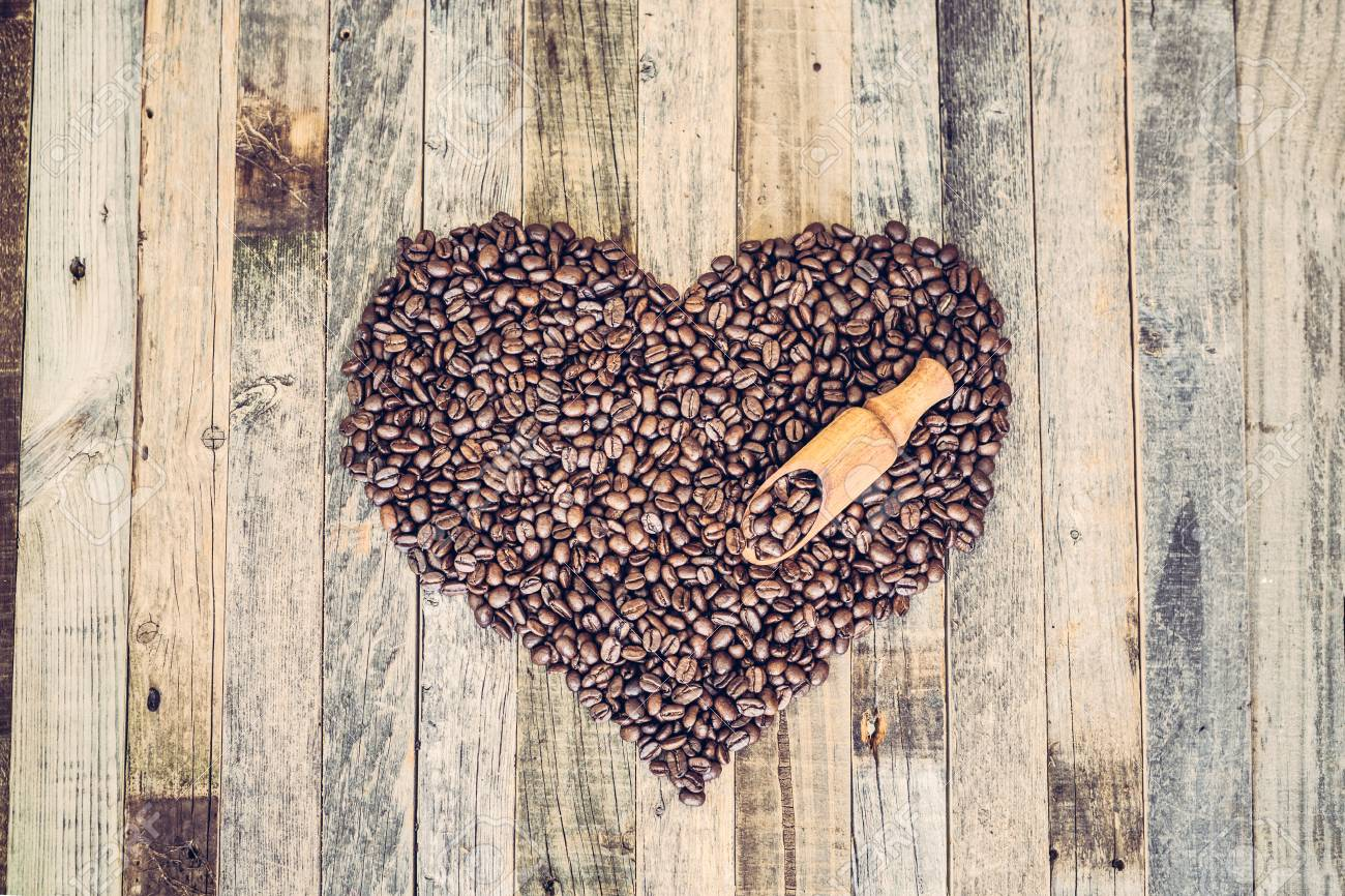 Roasted coffee beans in a shape of heart on wooden background - 97426327