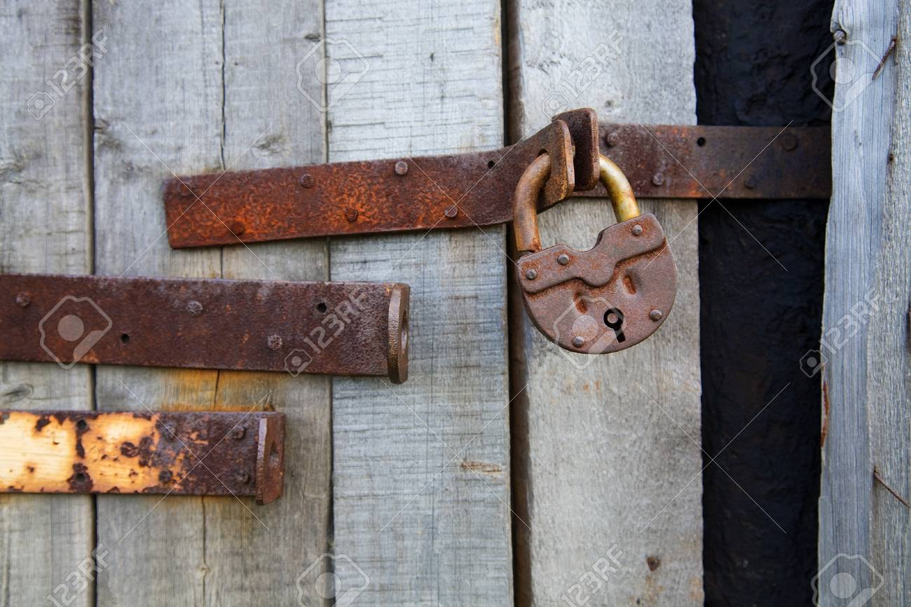Old rusty padlock on wooden grey background Stock Photo - 4288359
