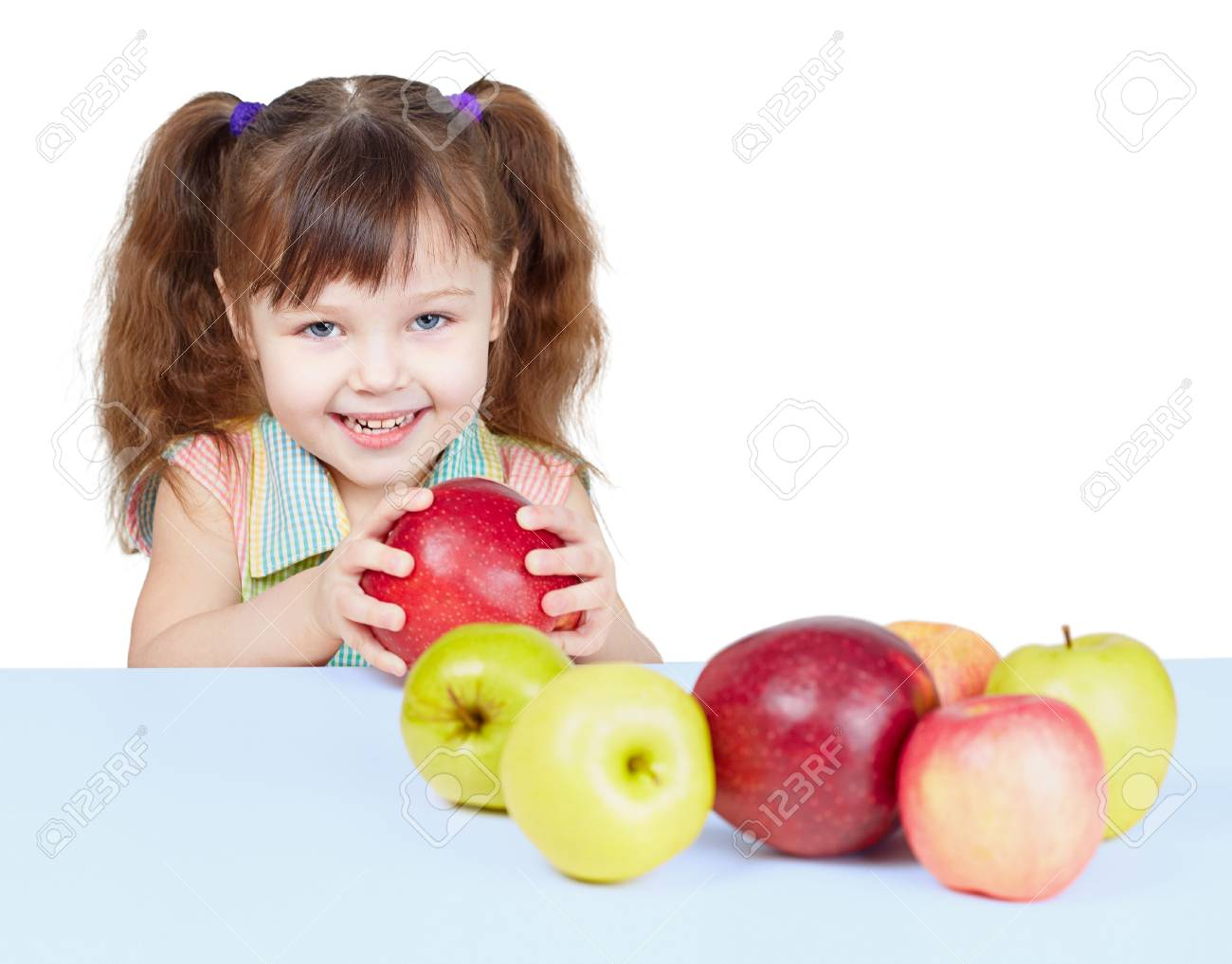A little girl playing with fruits sitting at the table Stock Photo - 6777424
