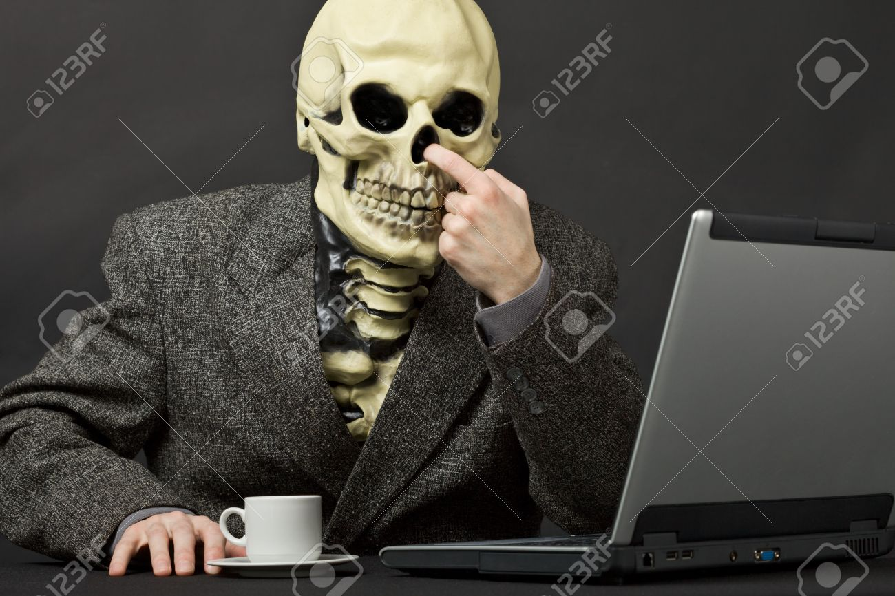 The skeleton picks in a nose on table with laptop Stock Photo - 7541287