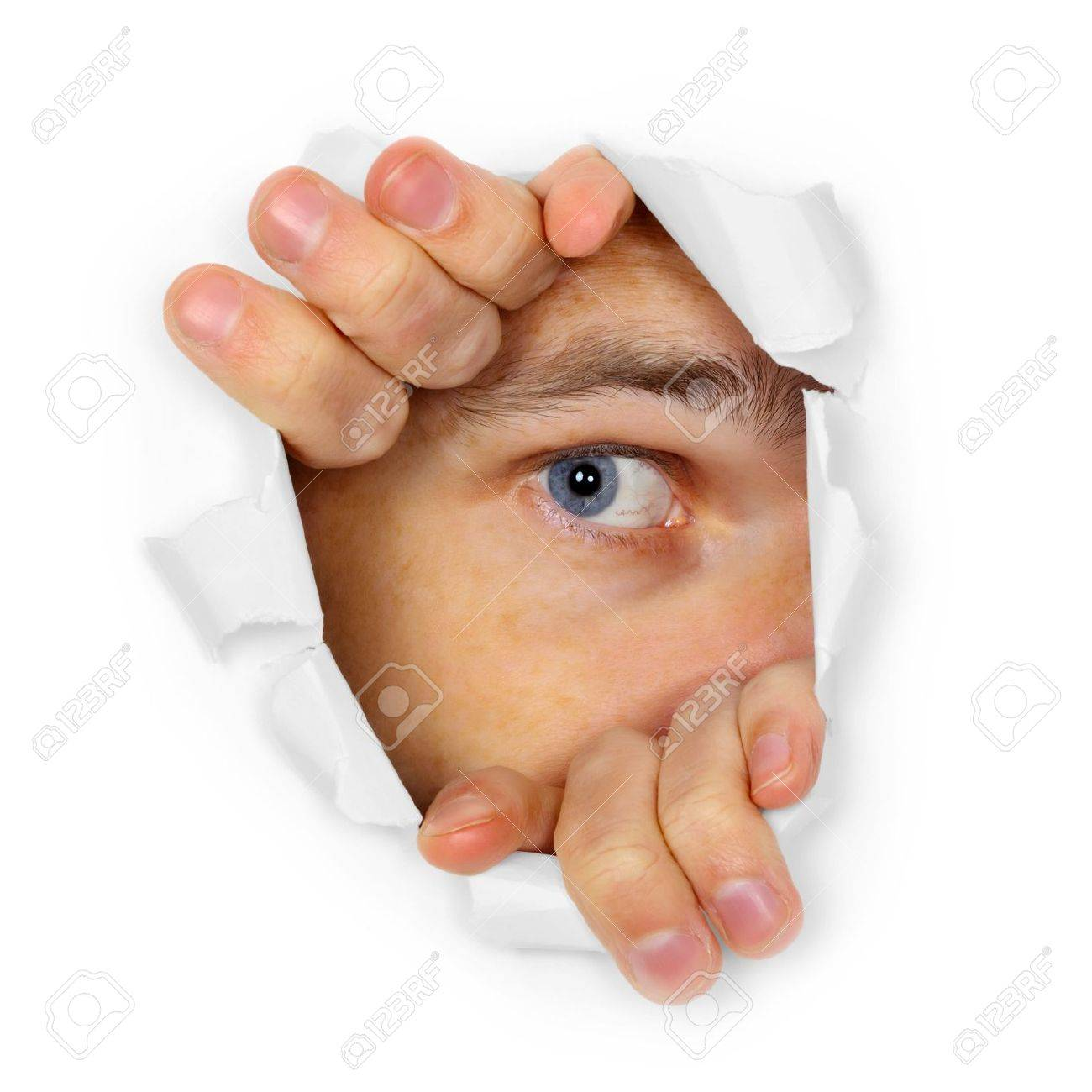 A man watches through a hole in the paper Stock Photo - 13977141