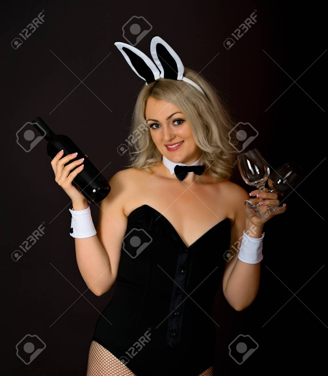 Young blonde with a bottle of wine and glasses on a dark background Stock Photo - 13977109