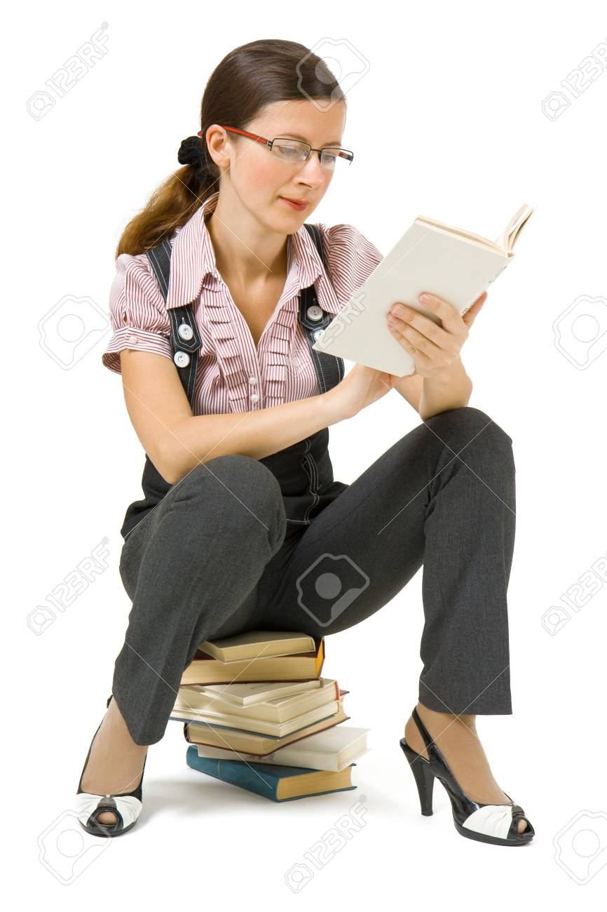 young girl with glasses sitting on a pile of books and reading Stock Photo - 7850660