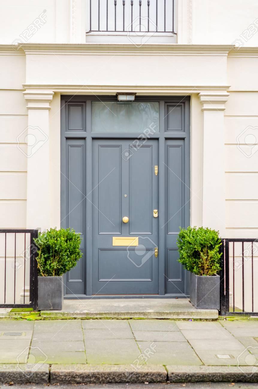 Entrée moderne de l\'immeuble avec murs élégants, balustrades des deux côtés  de l\'entrée, pots en métal carrés avec plantes vertes, entrée du trottoir  ...