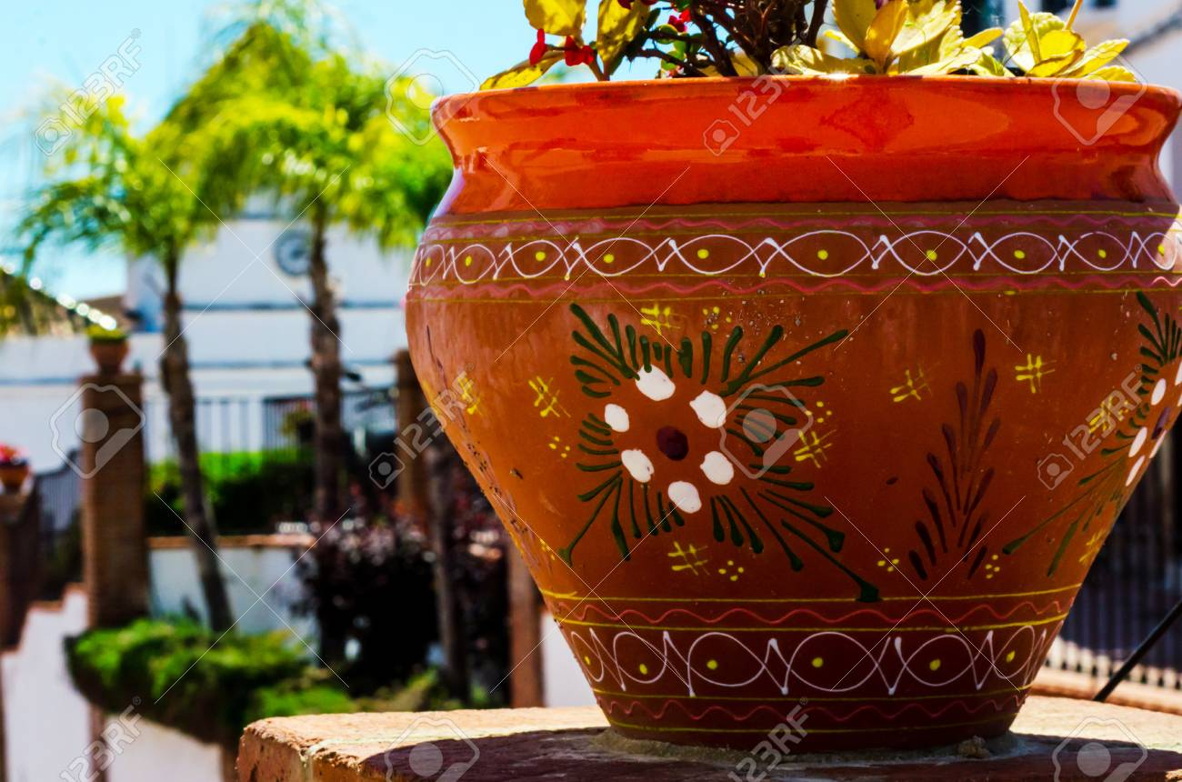 123RF.com & Beautiful ceramic flower pot on a pedestal with flowers decoration..