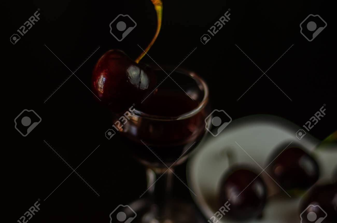 Cherry liqueur and juicy ripe cherries on the table in the bar,