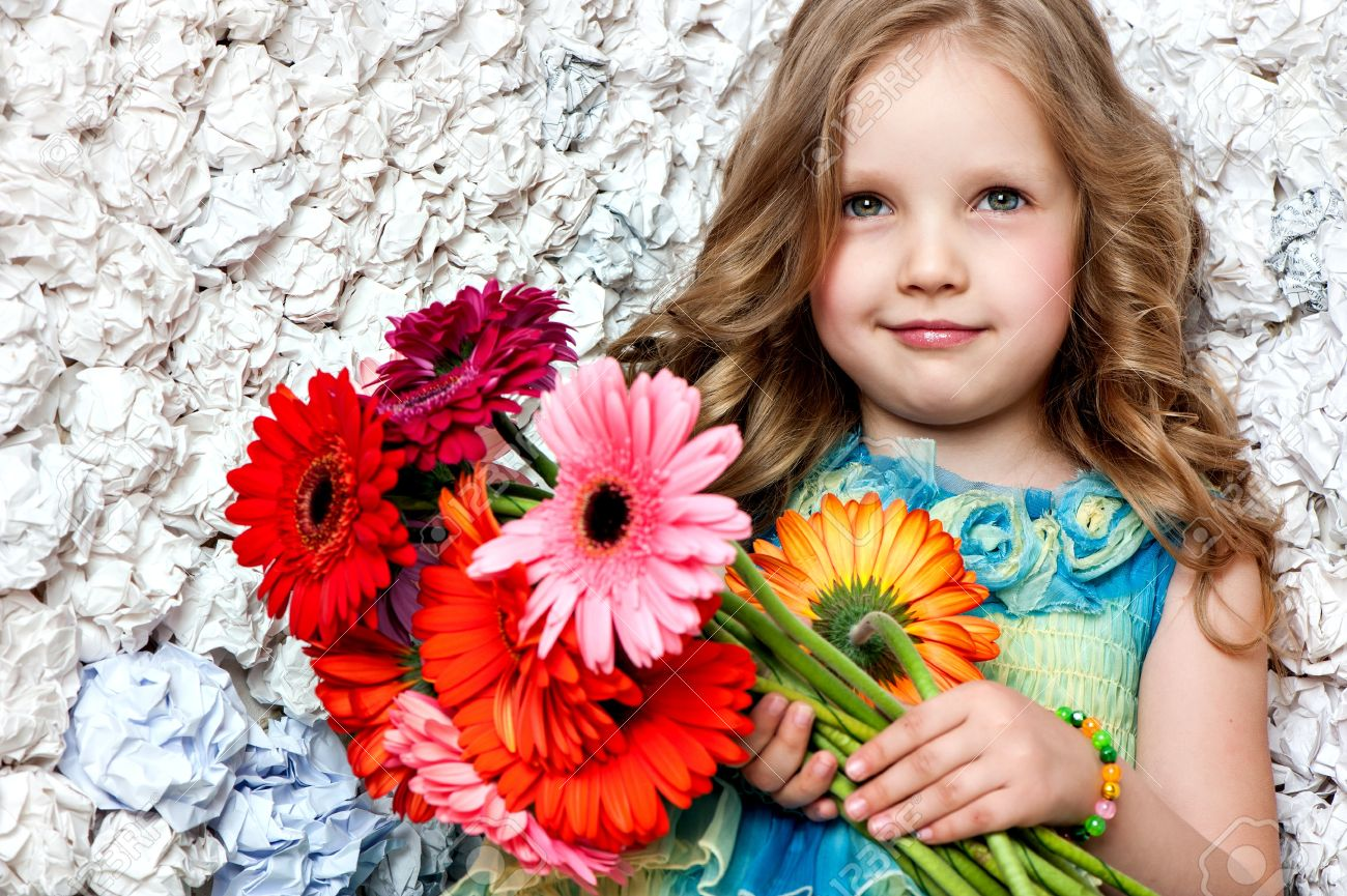 Fashion baby face beautiful child with fair hair in a pink dress holds flowers stock photo