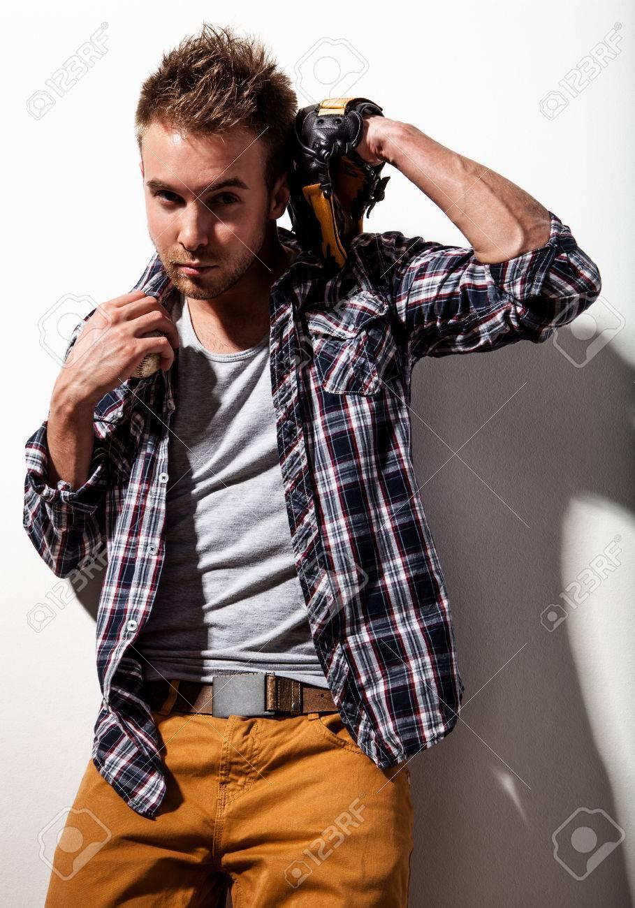 Belle homme de sport avec une barbe en chemise à carreaux, T shirt gris, un pantalon brun pose tenant un gant de baseball sur fond blanc