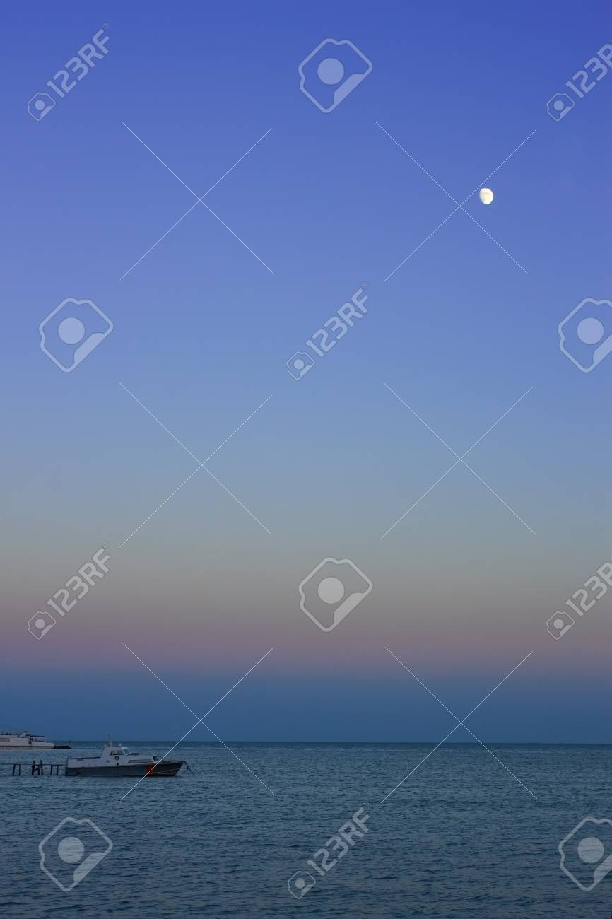 Night at sea. The moon in the cloudless sky illuminating motor boats near a pier Stock Photo - 14844969