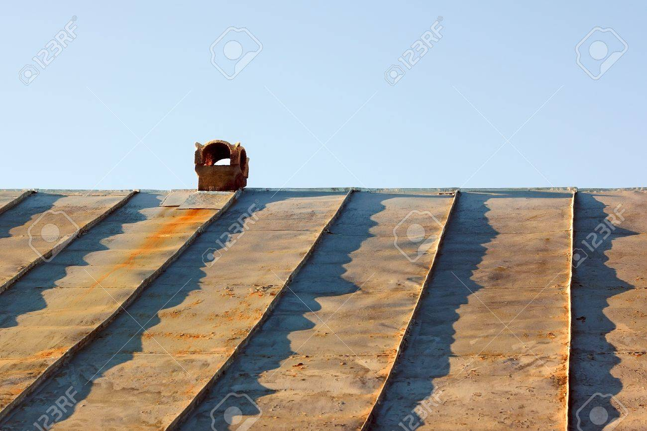 Chimney on an obsolete tinny roof against the blue sky Stock Photo - 15931090