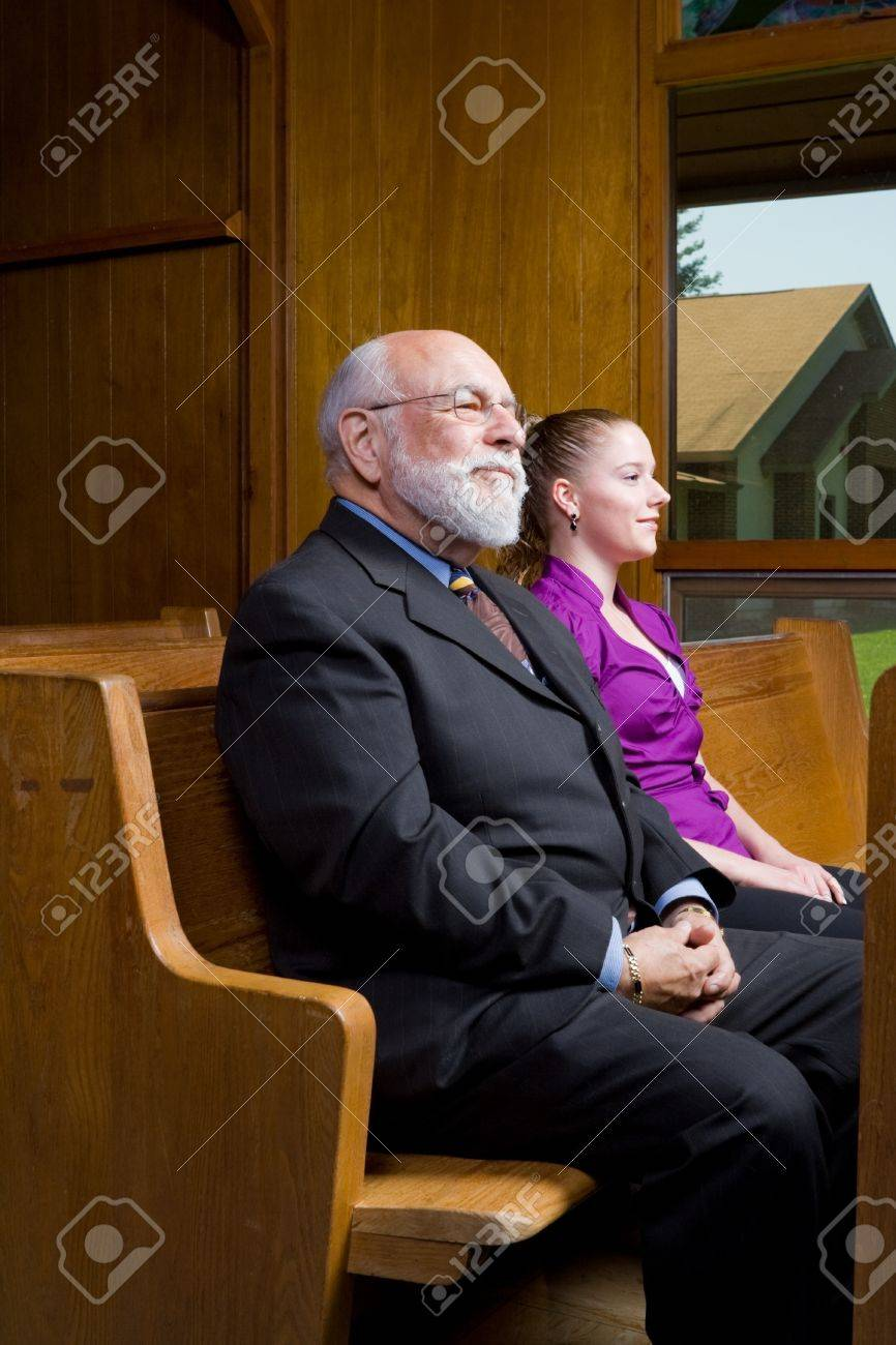 Older man and younger woman sitting in church Stock Photo - 9174368