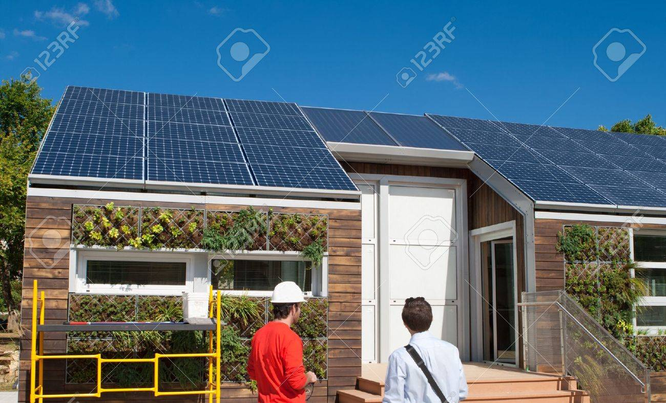 Solar construction workings looking at the roof.  Plants are from a gray water recovery system. Stock Photo - 11044591