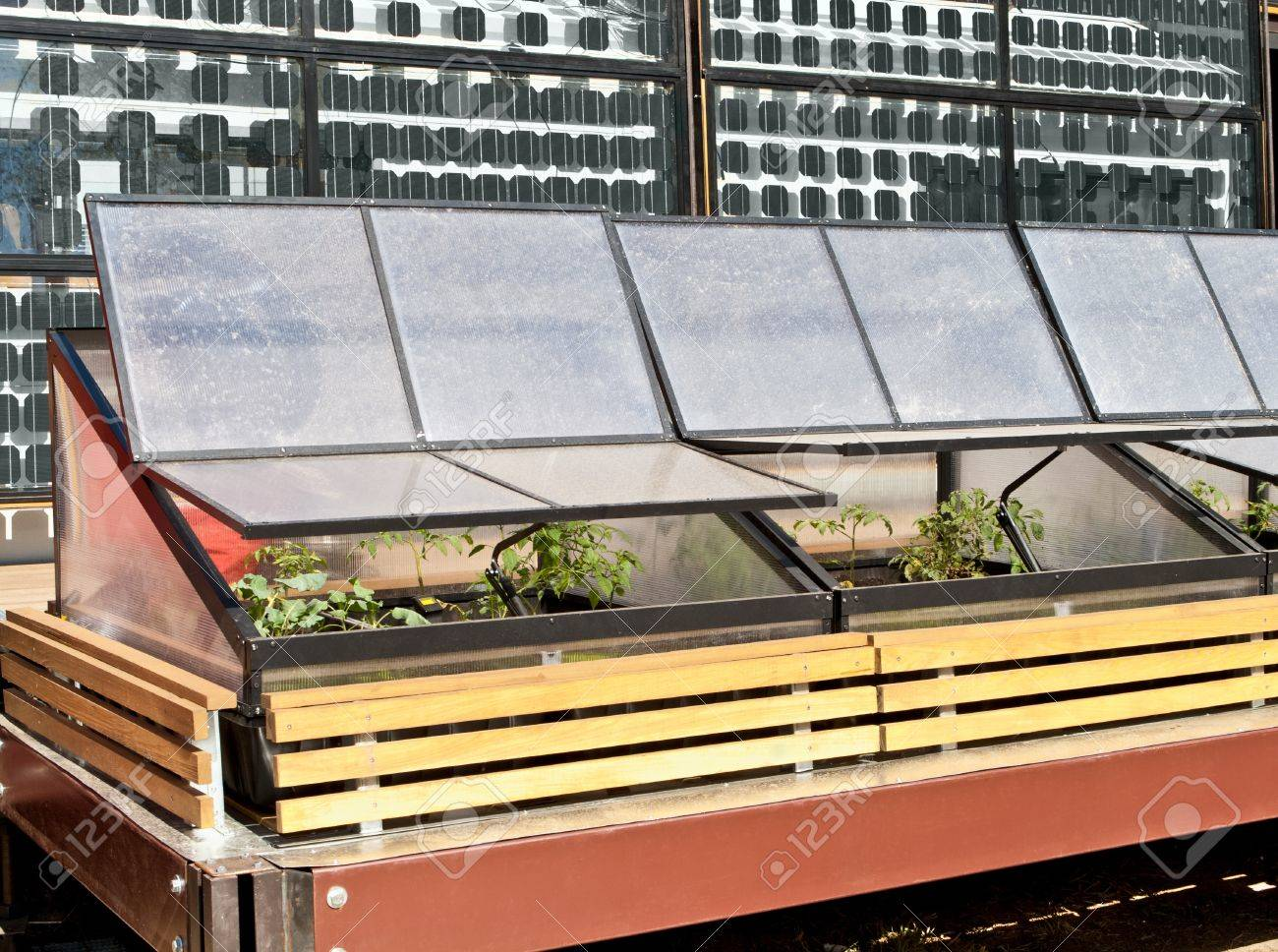 greenhouse cold frame and solar panels stock photo