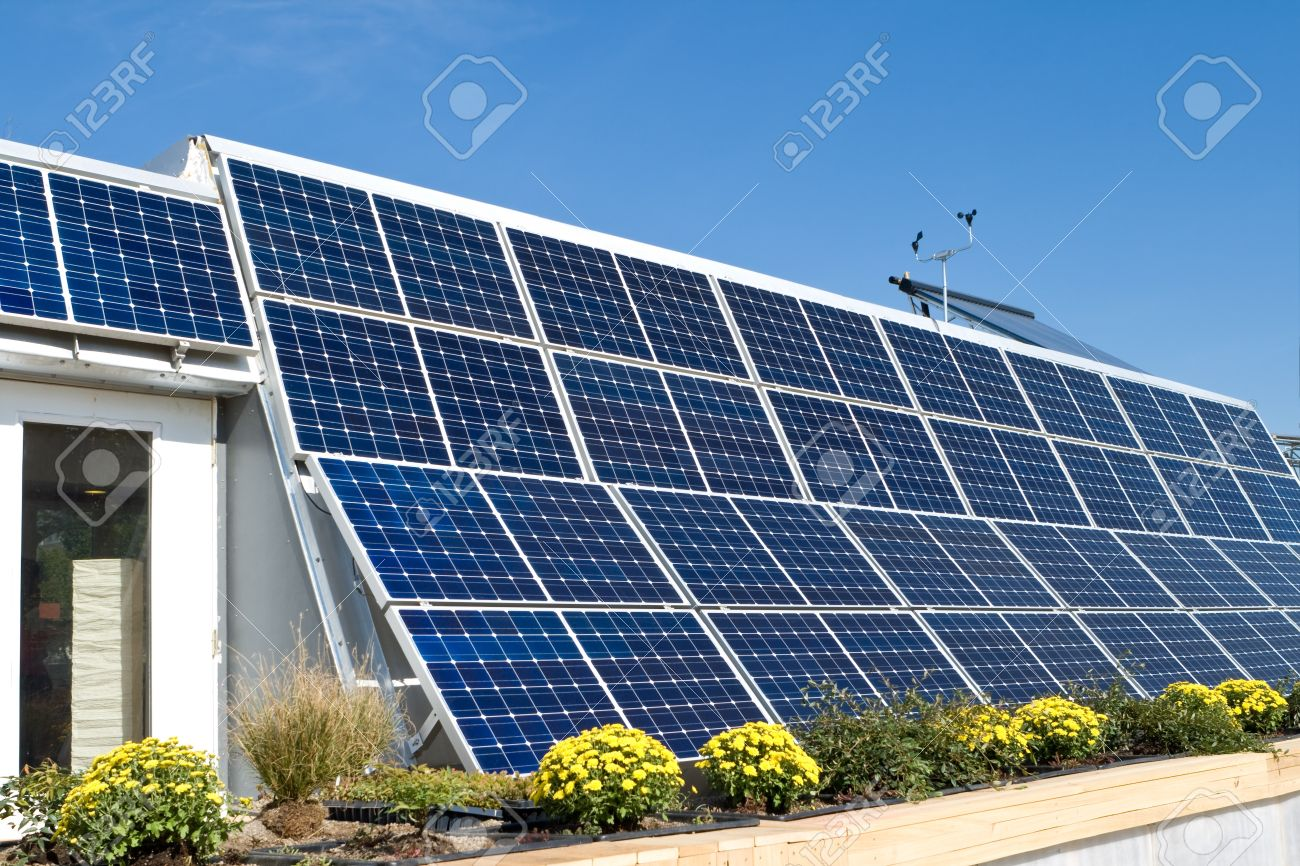 Exterior modern solar home with a row of photovoltaic solar panels and a solar hot water heater to the far right on the roof.  Anemometer on the roof as well. Stock Photo - 11379592