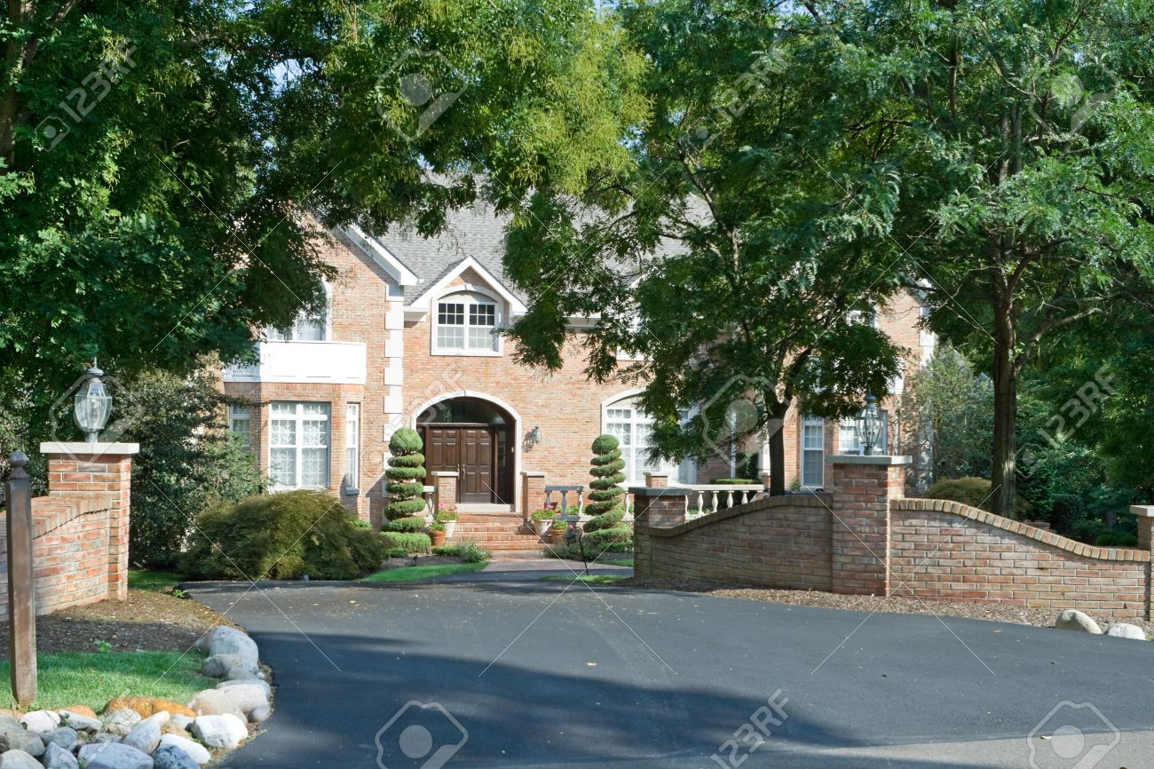 Upscale single family house with extensive landscaping and gate in suburban Philadelphia, PA.  House framed by trees. Stock Photo - 11379613