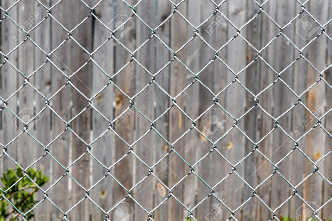 The Texture of Rhombic cells of a white metal lattice is in the sunny day in the summer park on the gray wood background - 170075933