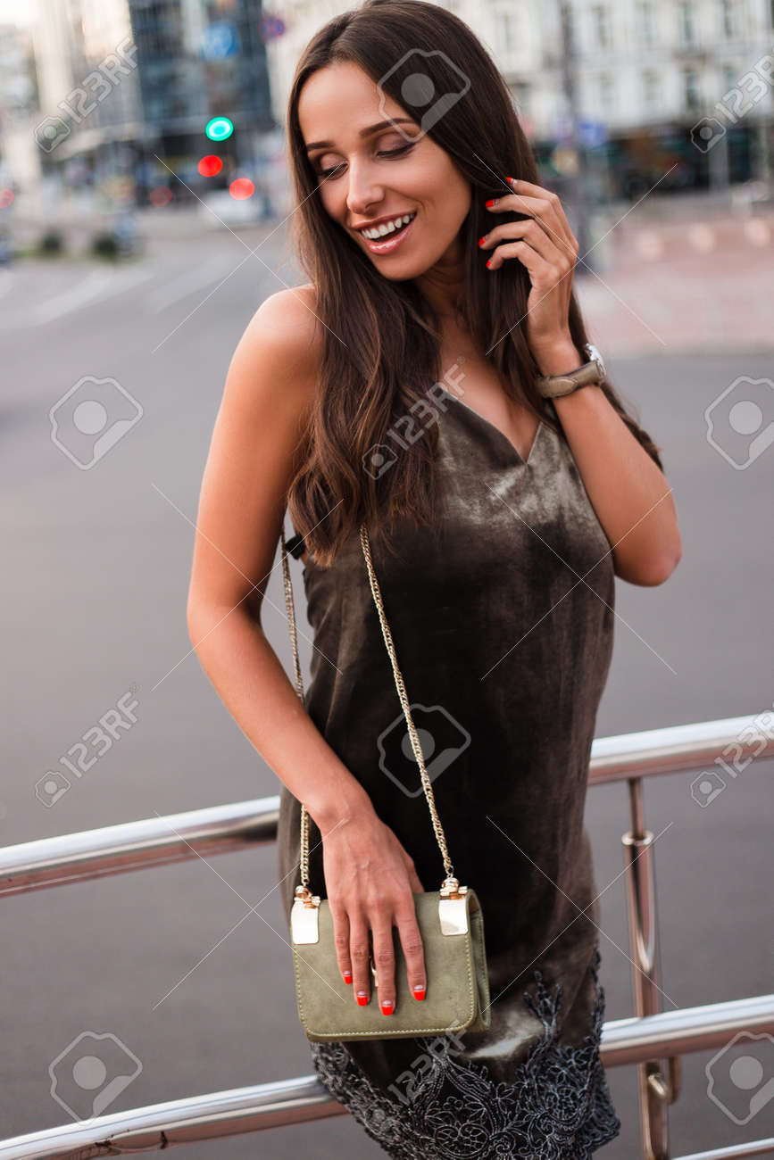 Soft beauty. Beautiful young woman in velvet dress keeping eyes closed with smile while standing outdoors - 159264125