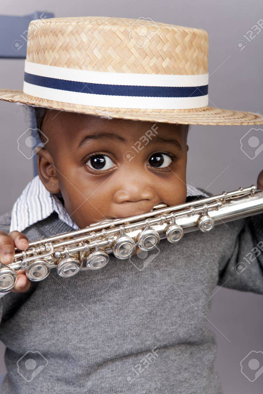 toddler holding silver flute in mouth wearing straw hat