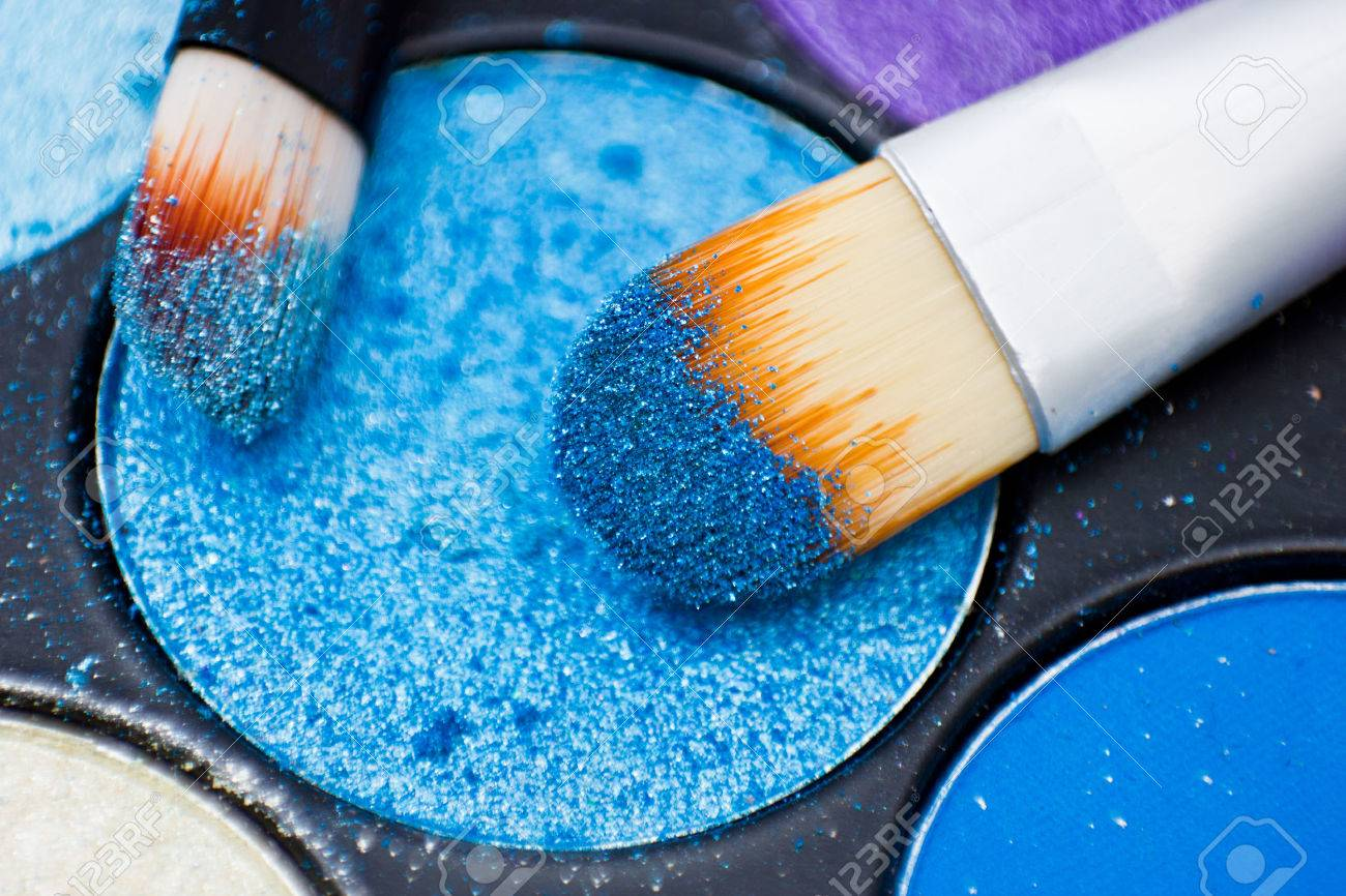 Brushes for make-up on the eye shadow palettes. Texture of crumbly blue sparkling shadows. - 54661742