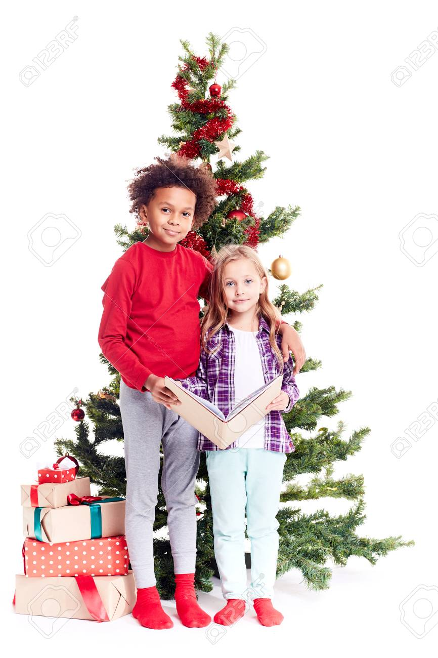 portrait of diverse brother and sister standing near christmas