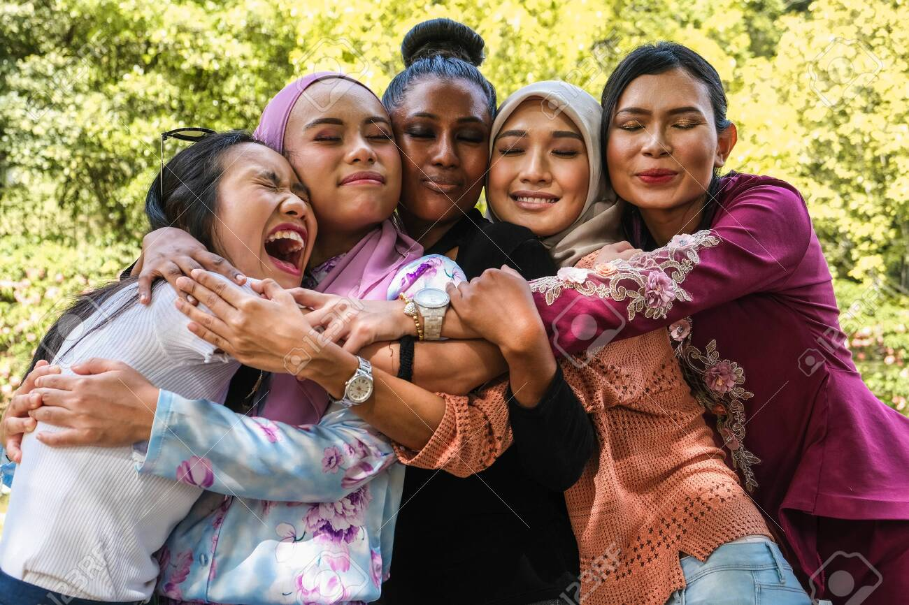 Five female friends of different ethnicity and faiths embrace each other in a group hug - 141194235