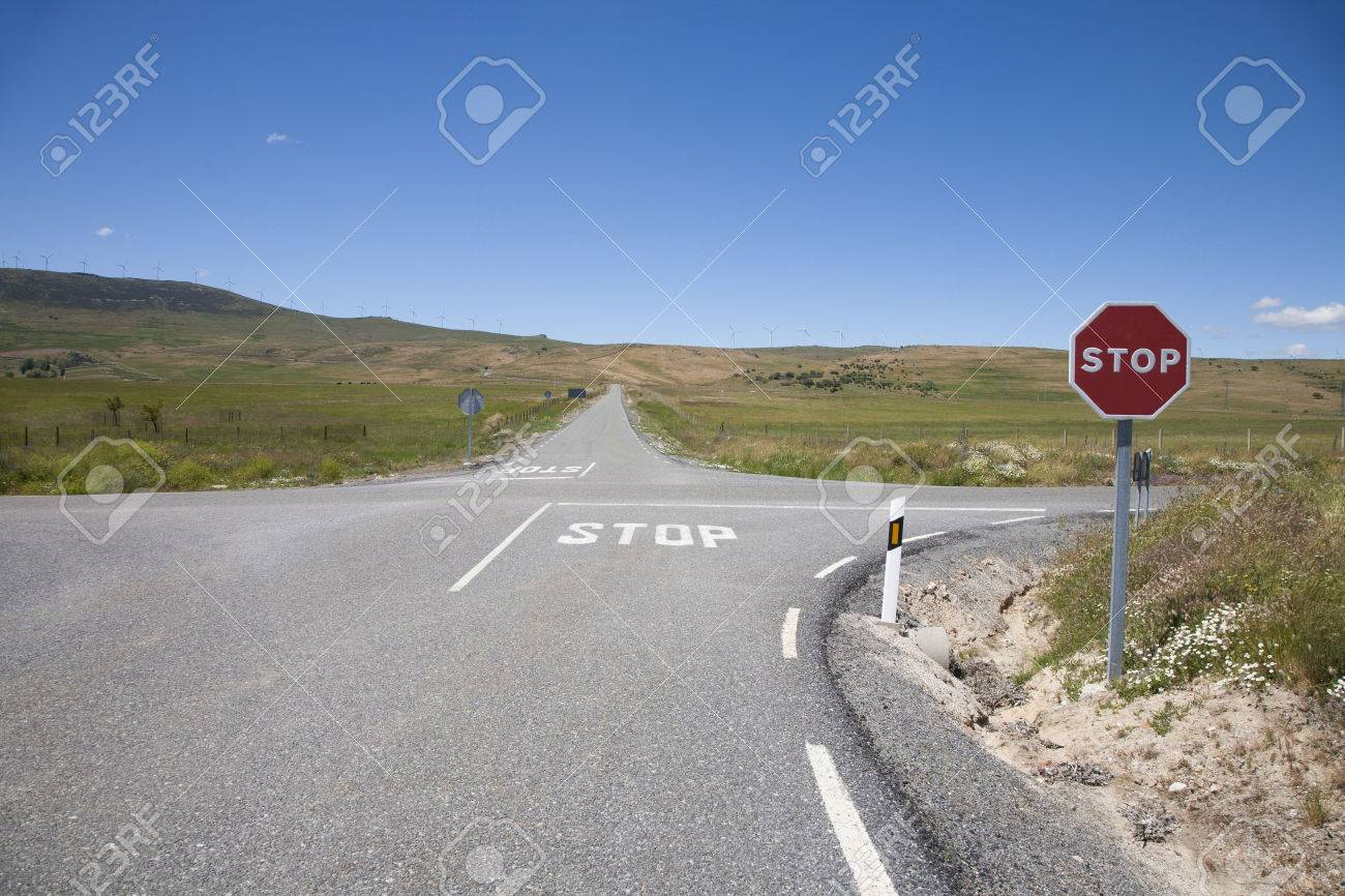 crossroad with stop symbol painted on asphalt and red hexagonal signal metal pole in rural road next to Madrid Spain Europe - 41689708