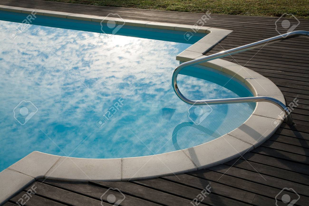 beautiful detail of swimming pool with cloudy sky reflected on..