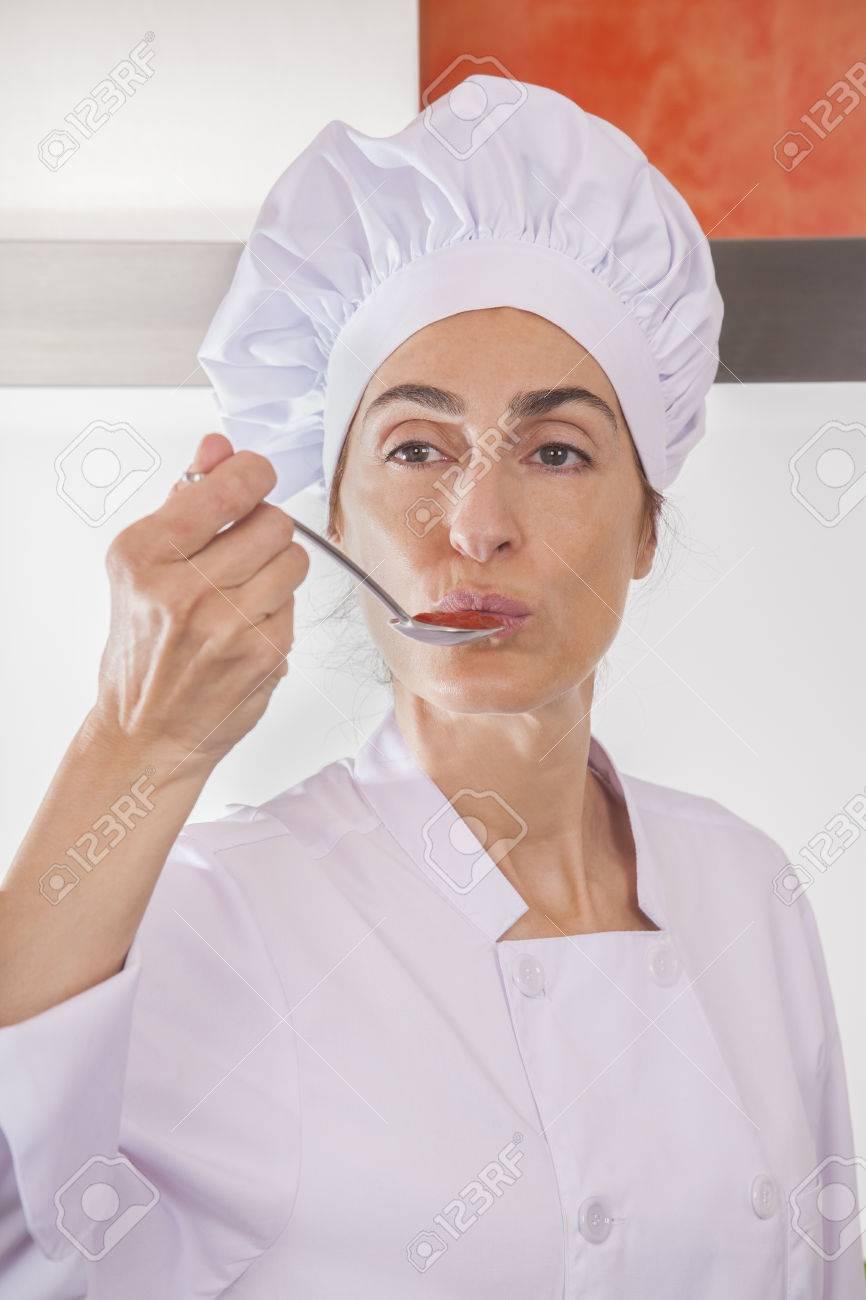Ritratto di donna chef con giacca e cappello professionale degustazione salsa rossa o crema purè come ketchup di pomodoro in un cucchiaio da minestra