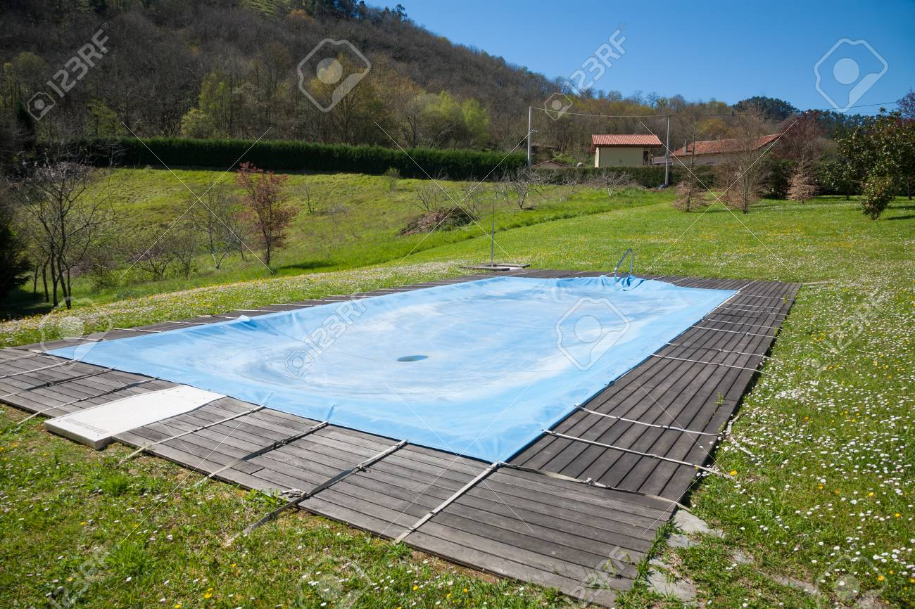 swimming pool with wooden curb closed and covered with blue tarp..