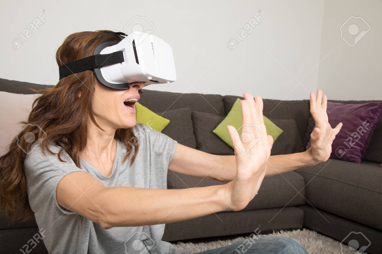 brown hair adult woman with virtual reality headset, or 360 glasses, grey  shirt,