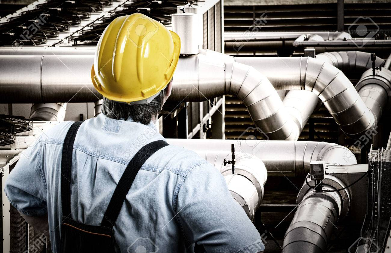 Worker in protective uniform and protective helmet in front of industrial pipes - 50858401
