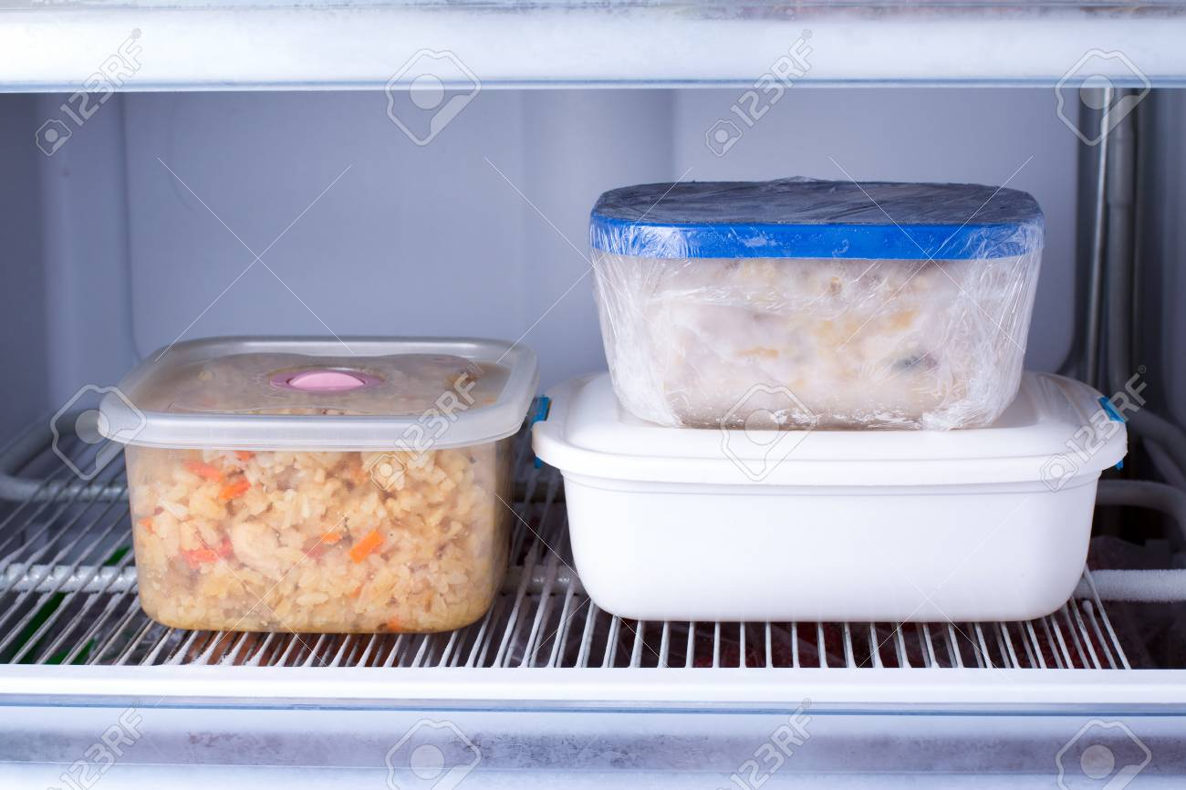 Frozen food in a container in the freezer. Refrigerator with frozen food. Ready meal - 97657890
