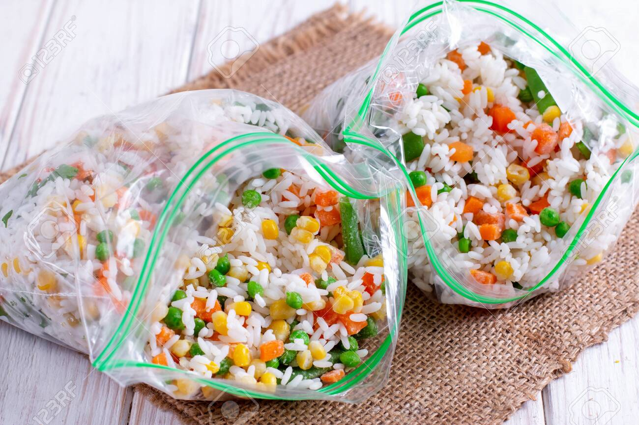 Frozen mixed vegetables in freezer bag. Frozen vegetable mix with rice - 126936295