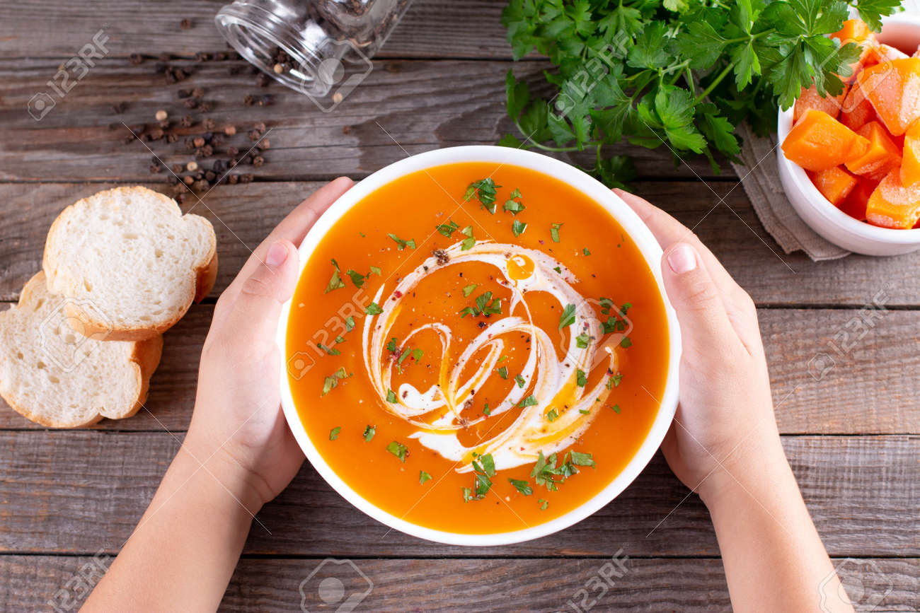 Kids hands holding a bowl with pumpkin soup on wooden background. Healthy eating concept. Top view. - 157343756