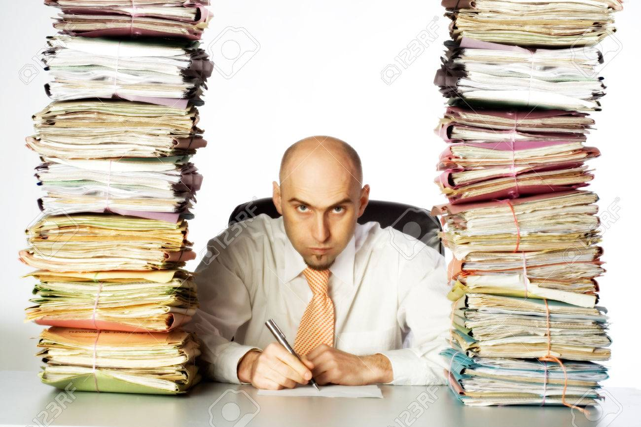 A stern and unpleasant administrative clerk glares through two huge stacks of business files, clearly indicating he has not time or desire to be of any customer service. Stock Photo - 1498124