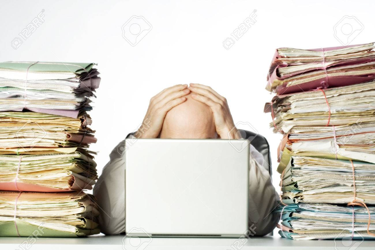 Male businessman sitting behind a laptop, his face hidden, with his hands on top of his head.  Two large piles of paperwork are piled on each side of the model, towering over his head.  Isolated on white background. Stock Photo - 1693306