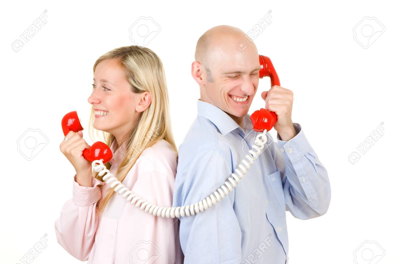 Happy young couple connected with red retro style telephones; white studio background. Stock Photo - 9526315