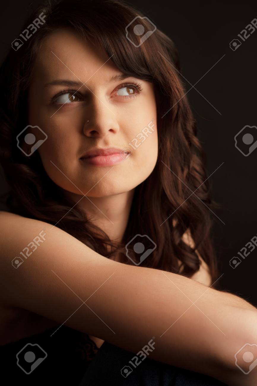 Portrait of a brunette woman with long hair on a dark background. Stock Photo - 9526643