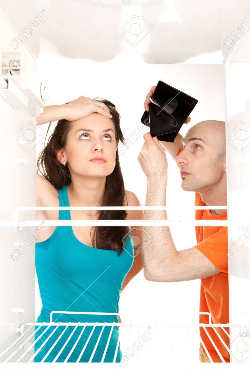 A couple with no money searching for food in an empty refrigerator whilst the man holds his empty wallet. Stock Photo - 9526781