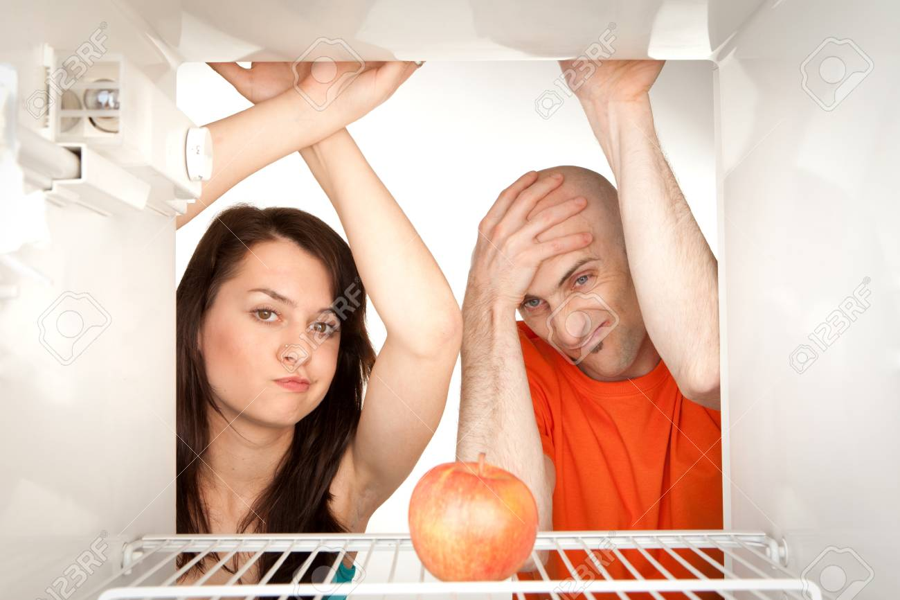 Young couple looking at ripe apple in otherwise empty refrigerator. Stock Photo - 9526765
