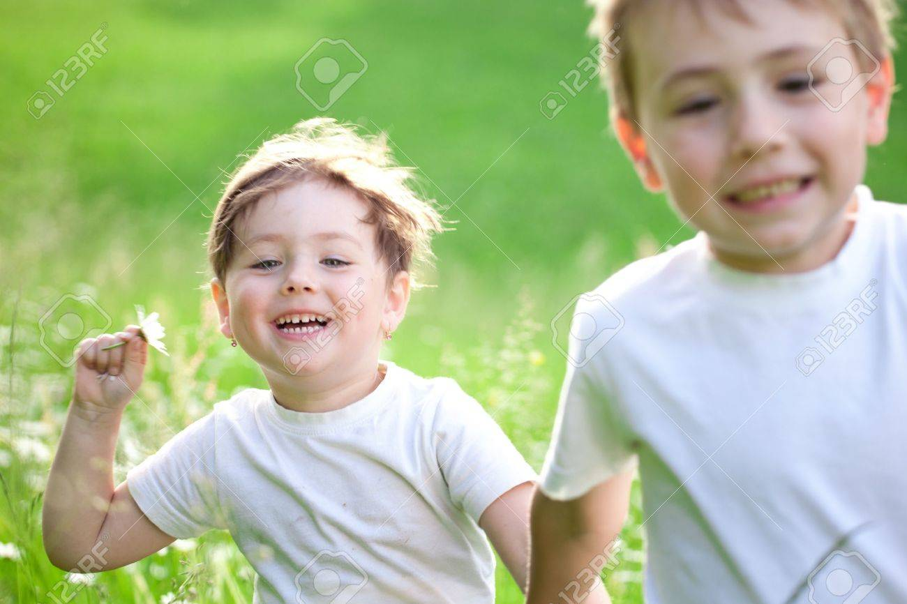 Two cute young preschool, child running and playing in green field. Stock Photo - 10069911