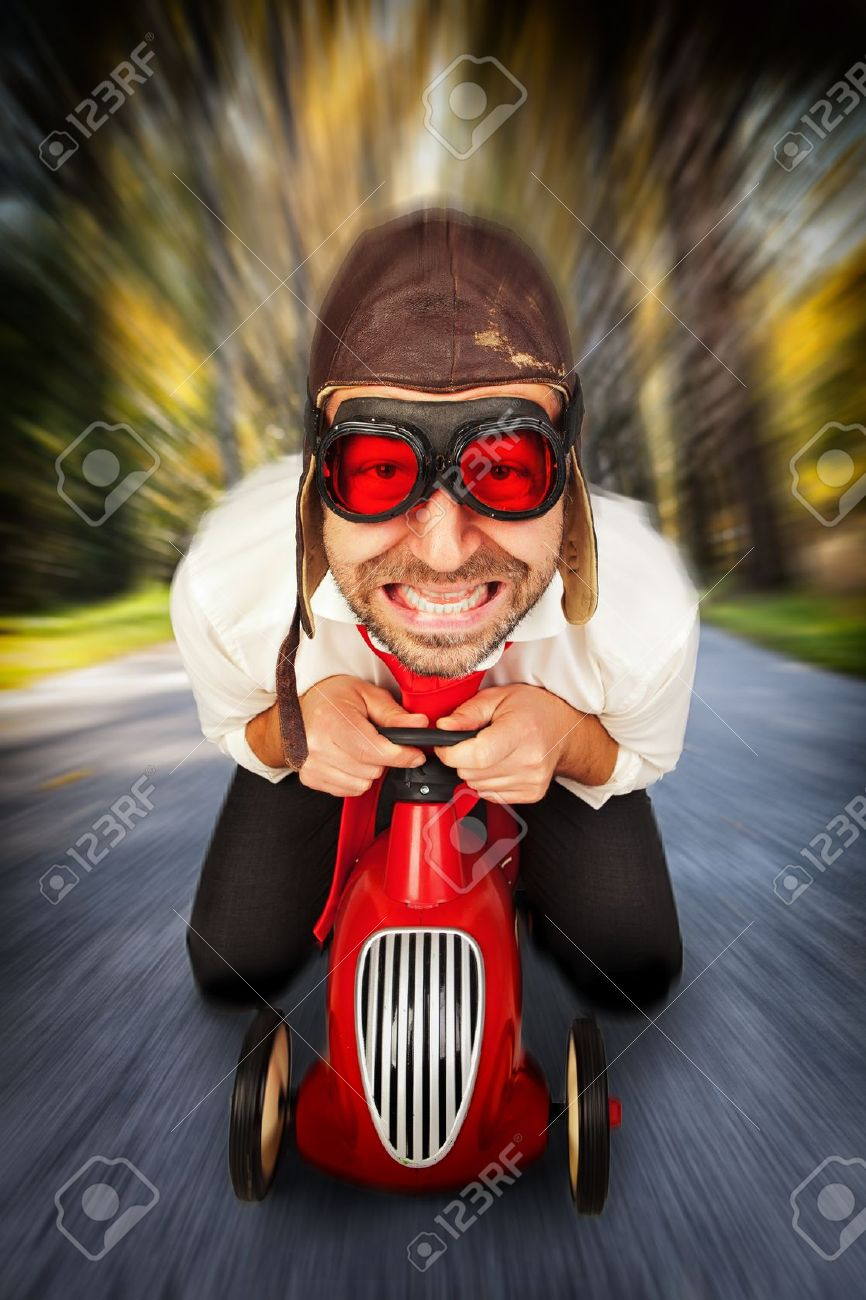 Man in retro racing hat and goggles driving on toy car at speed with blurred background. - 17374682