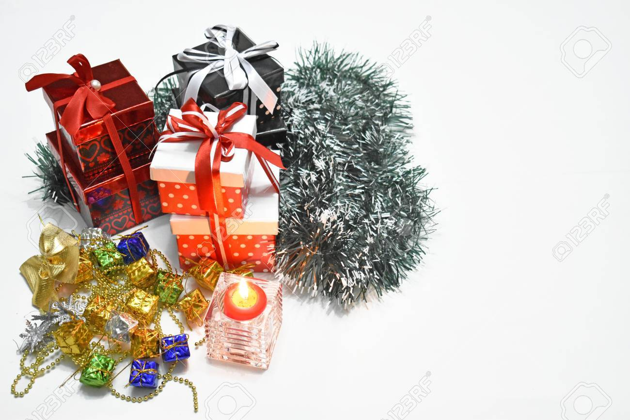 Christmas gift packages with ribbons and burning candle isolated